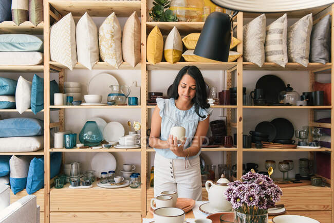 Woman turning to inspect handmade mug in small home goods store — Stock Photo