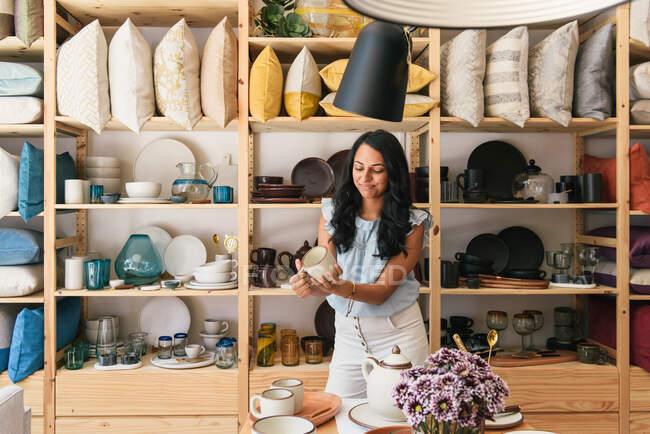 Посміхнена жінка дивиться на виготовлену вручну керамічну чашку для кави в бутик-магазині. — стокове фото