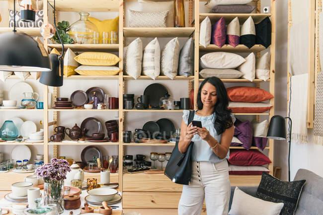 Elegante donna controllare i messaggi sul telefono durante lo shopping in negozio — Foto stock