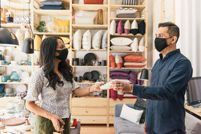 Customer and business owner smiling at each other making purchase — Stock Photo
