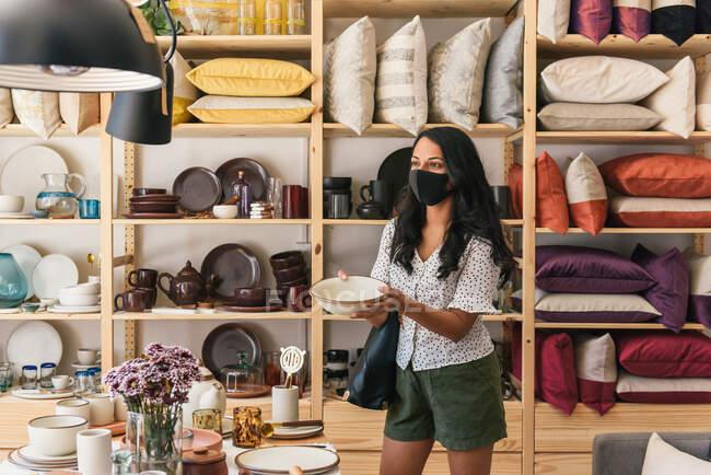 Стильный покупатель в маске собирает миску в роскошном магазине — стоковое фото