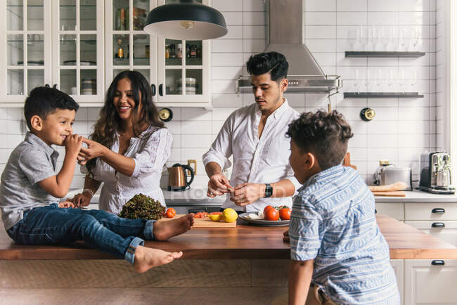 Young happy family spending time with kids — Stock Photo