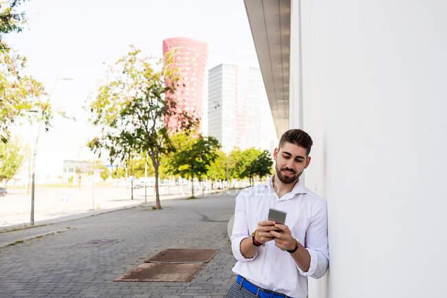 Молодой бородатый мужчина прислонился к белой стене с помощью мобильного телефона — стоковое фото