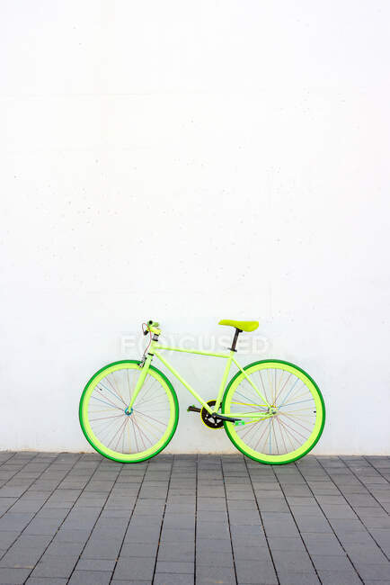 A green vintage city bicycle fixed gear on white wall — Stock Photo