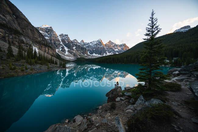 Hermoso paisaje de lago de montaña, chica sentada en la roca - foto de stock