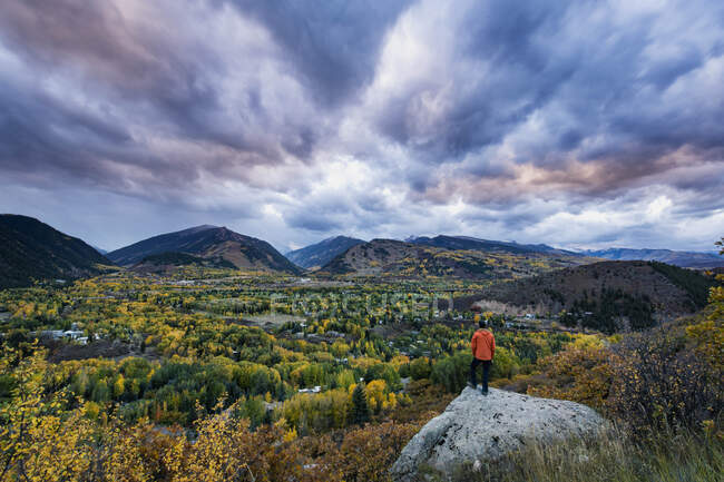 Rear view of male hiker standing on rock against cloudy sky during sunset — Stock Photo