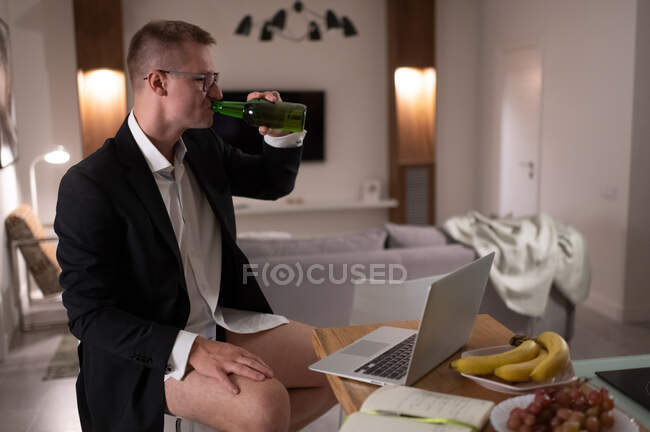 Half dressed businessman sipping beer while taking break in telework at home — Stock Photo