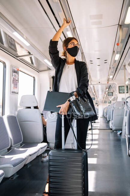 Young businesswoman in face mask carrying folder and bag and grasping handlebar while commuting to work by train — Stock Photo