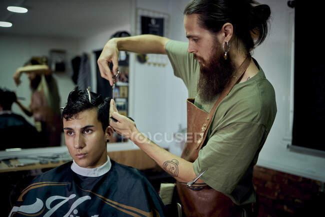 Un uomo barbuto che taglia i capelli a un giovane uomo moderno. Concetto di barba — Foto stock
