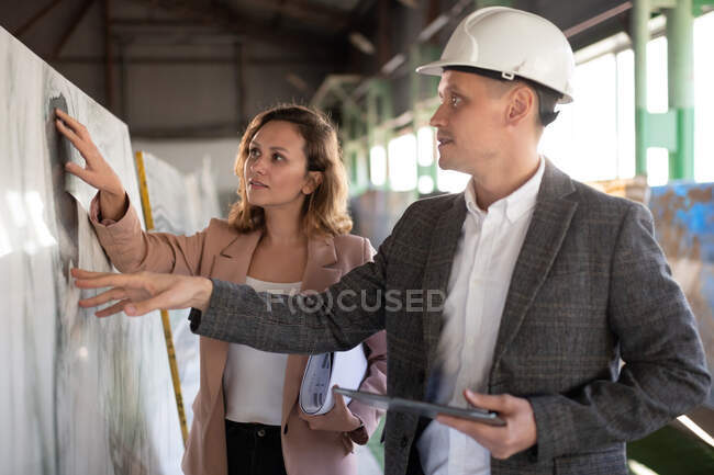 Side view of adult businessman and businesswoman in jackets picking slab of natural marble in industrial warehouse of stone company — Stock Photo