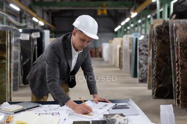 Moderne männliche Arbeiter in Bollenhut lehnen sich über den Tisch, während sie an einem Projekt in der geräumigen Lagerhalle der Marmorproduktionsfirma arbeiten — Stockfoto