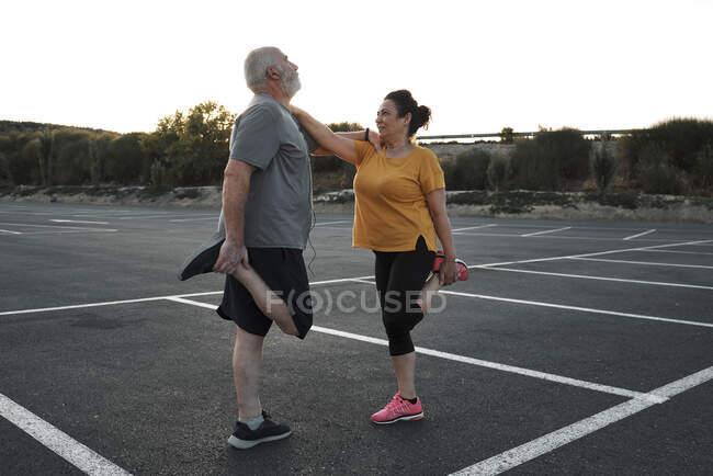 Una pareja de mediana edad están haciendo ejercicios de estiramiento juntos. - foto de stock