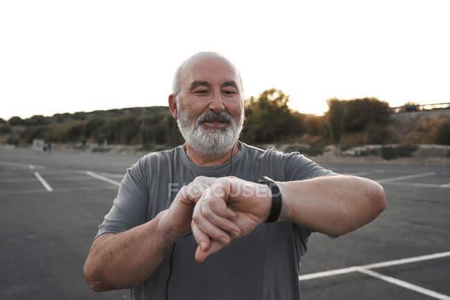 Старик с седыми волосами и бородой смотрит на свои умные часы — стоковое фото