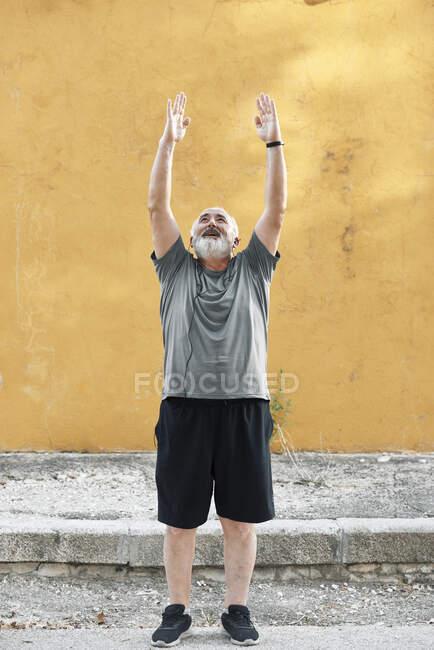 Толстый пожилой мужчина растягивается перед стеной. — стоковое фото