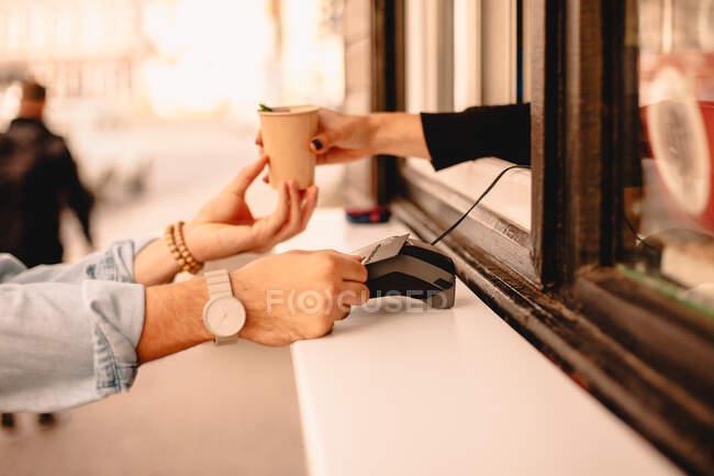 Женщина-бариста дает кофе клиенту, который делает оплату кредитной картой — стоковое фото