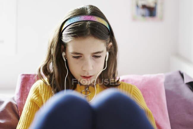 Девушка лежит на кровати, смотрит на планшет и носит наушники. — стоковое фото