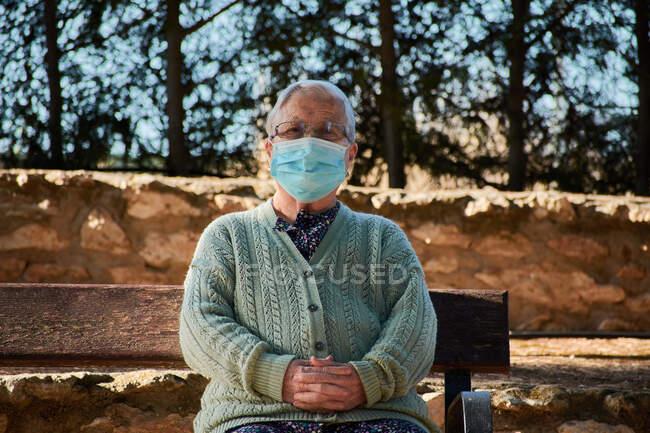 Ältere Frau sitzt mit Maske auf einer Parkbank — Stockfoto
