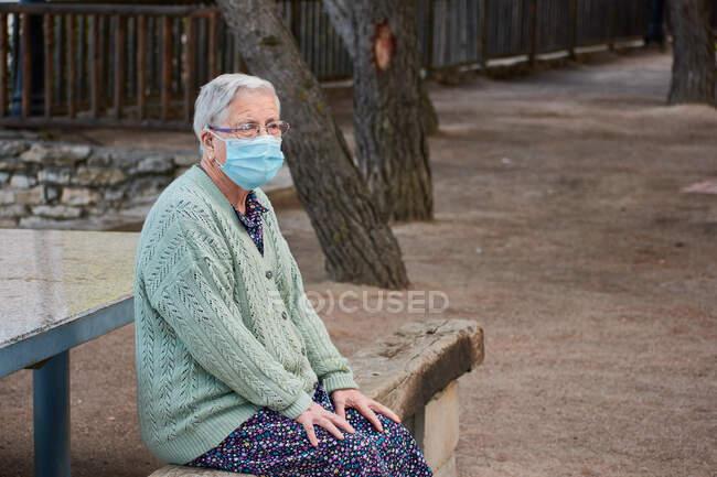 La nonna è seduta su una panchina con la maschera — Foto stock
