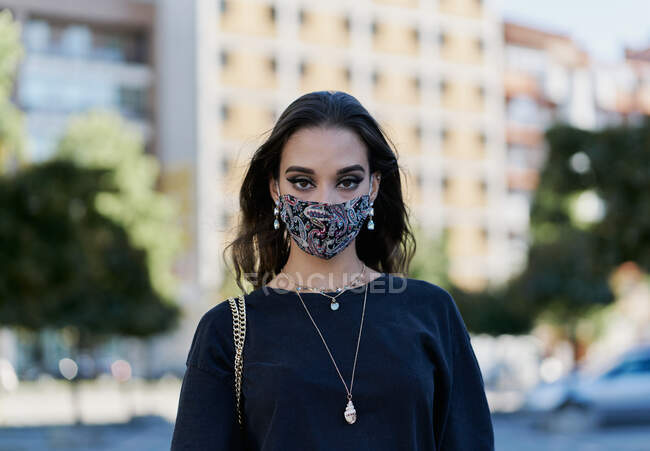 Vista frontal de um retrato do rosto de uma jovem menina da cidade com uma máscara escura e roupas pretas — Fotografia de Stock