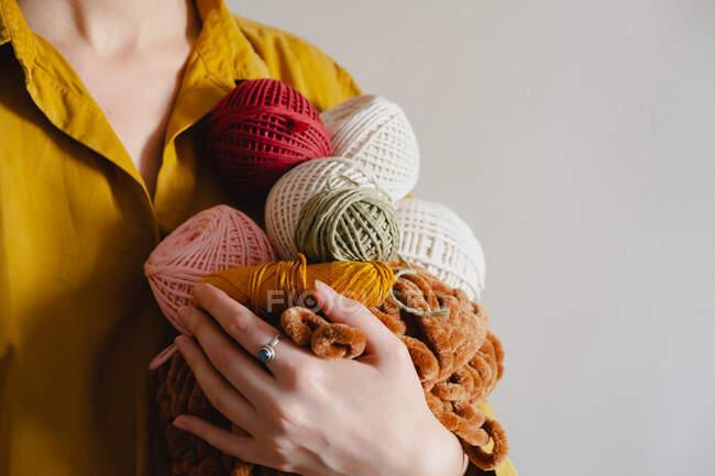 Rolos de cordas de algodão na mão da mulher. Tricô, crochê, conceito de passatempo artesanal — Fotografia de Stock