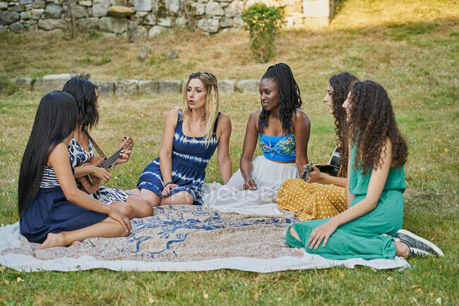 Smiling woman playing guitar having fun with group of friends — Stock Photo