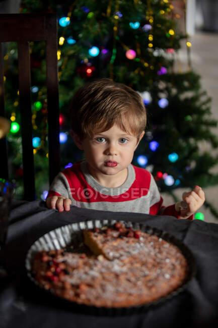 Il bambino che mangia bacche forma una torta su un tavolo in Natale — Foto stock