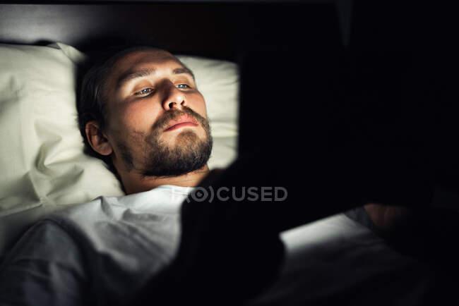 Giovane uomo bello e stanco con la barba non riesce a dormire e sta guardando qualcosa sul suo tablet di notte. — Foto stock