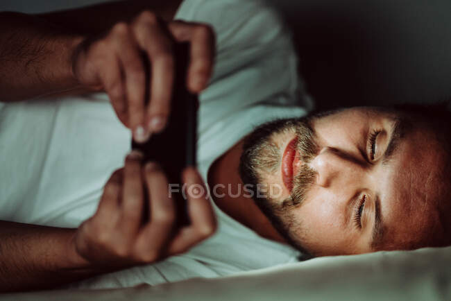 Young happy man cannot sleep and is watching something on his phone at night. White light from the phone is all over his face. — Stock Photo