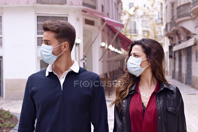 Jovem casal com máscara facial nas ruas da cidade — Fotografia de Stock