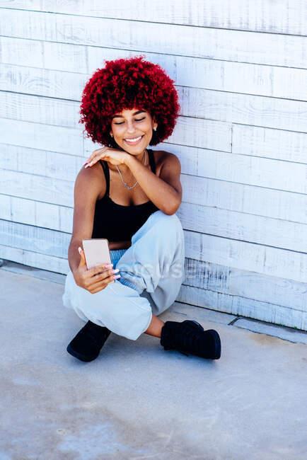 Donna con capelli afro rossi che si fa un selfie con il cellulare — Foto stock