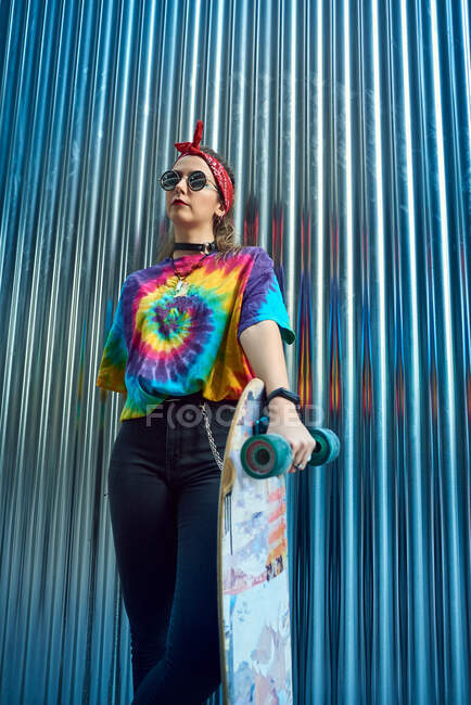 Young woman with urban style, she poses with a long board. — Stock Photo