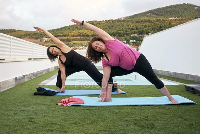 Frauen machen Yoga auf der Terrasse des Hauses, Dreieckshaltung — Stockfoto