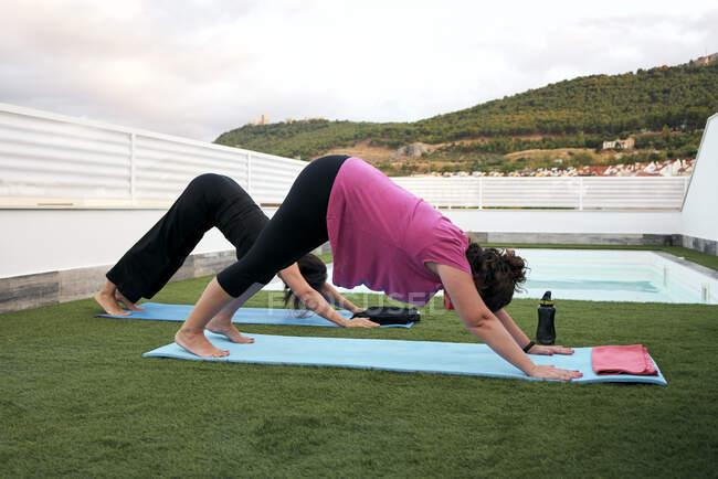 Frauen machen Yoga auf der Terrasse des Hauses, verdecken Hundehaltung — Stockfoto