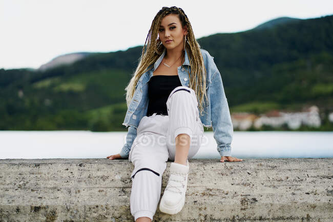 Young woman with blonde braided hair wearing a denim jacket and white jean resting on a bridge on a rainy day — Stock Photo