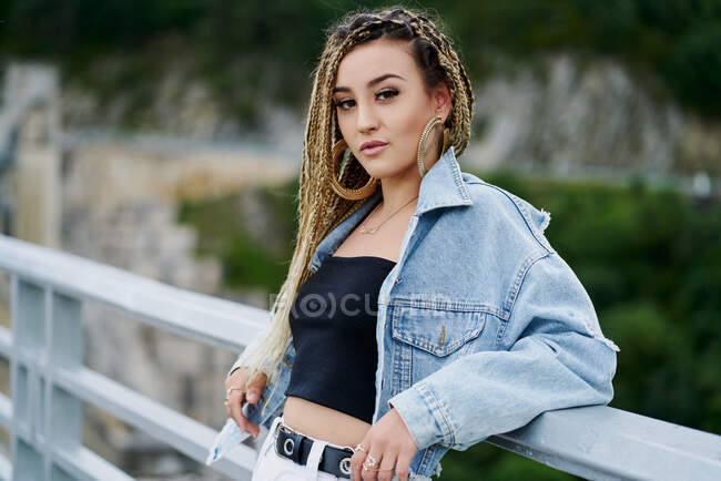 Young woman with blonde braided hair wearing a denim jacket and white jean resting on a bridge — Stock Photo