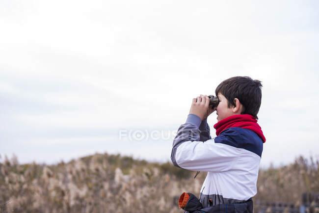 Грайливий хлопчик дивиться через бінокль, стоячи на дорозі. — стокове фото