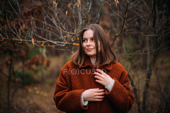 Close-up portrait of pretty young lady standing in park — Stock Photo