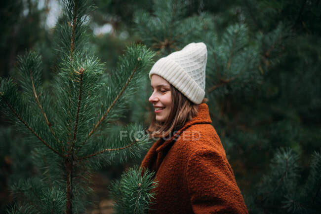 Pretty young woman in warm clothes standing and relaxing in park — Stock Photo