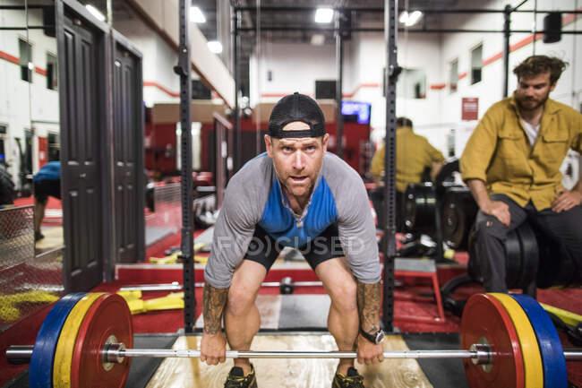 Чоловік, який будує свої фізичні вправи в спортзалі з особистим тренером — стокове фото