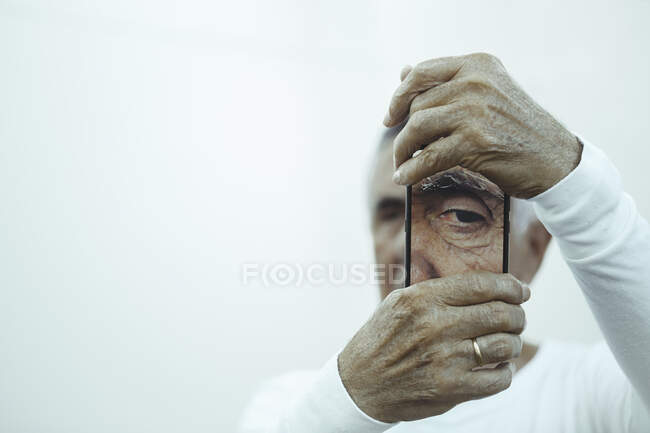 Senior man taking picture of eye on mobile device, creative concept — Stock Photo
