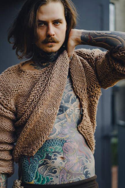 Нахабний татуювальний сексуальний чоловік з довгим волоссям і вусами на вулиці. — стокове фото