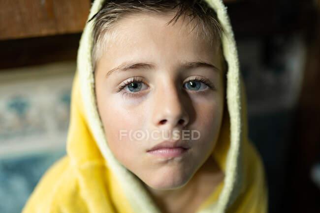 Pequeño niño de ojos azules sonriendo fuera del baño - foto de stock