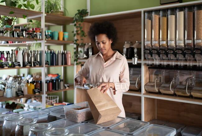 Этническая женщина упаковывает натуральную пасту в бумажный пакет во время работы в эко-магазине — стоковое фото
