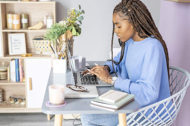 Young girl writing and working with the computer at home — Stock Photo
