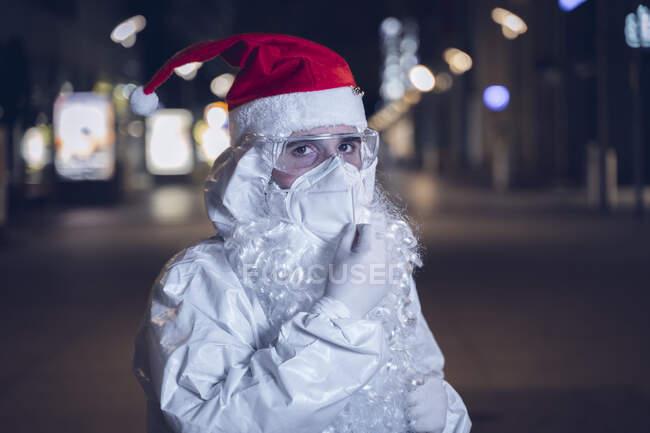 Портрет чоловіка, одягненого як Санта Клаус, але з усією охороною проти ковидки 19, сфотографований на обличчі маски.. — стокове фото