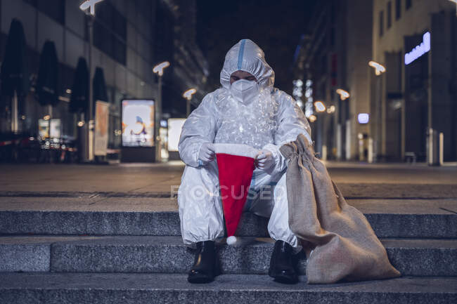 Foto de um mendigo, vestido no macacão usado contra o coronavírus, a máscara, e a barba e chapéu de Papai Noel, sentado nas escadas em um quadrado vazio. Olhe para dentro do chapéu vazio. — Fotografia de Stock