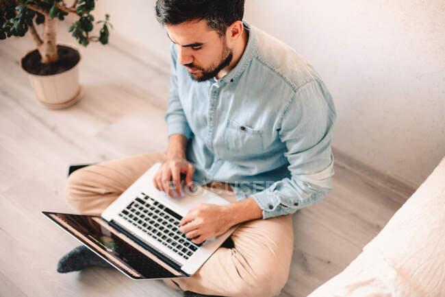 Hombre serio usando el ordenador portátil mientras está sentado en el suelo en casa - foto de stock