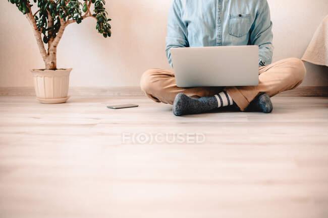 Mann benutzt Laptop, während er zu Hause auf dem Boden sitzt — Stockfoto