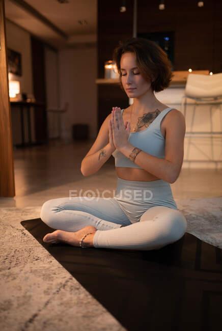 Посмішка жіночого жесту намасте і закрити очі під час медитації в позі Падмасани. — стокове фото