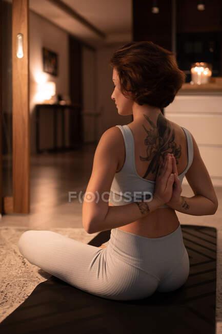 Задний вид молодой женщины, сидящей в позе Лотоса и медитирующей с сжатыми руками — стоковое фото